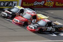 On lap 93, No. 51 Aric Almirola, No. 30 Todd Bodine and No. 18 Kyle Busch got three-wide across the start-finish line in the NASCAR Camping World Truck Series VFW 200 Saturday at Michigan International Speedway in Brooklyn, Mich. Credit: Jerry Markland/Getty Images for NASCAR